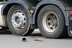 © Licensed to London News Pictures. 26/08/2020. London, UK. The victims slipper, face mask, and blood stains are seen in-between the wheels of a heavy goods vehicle outside Manor House underground station on Green Lanes, north London following an accident with an elderly man. An elderly man was seen crossing the road when he was hit by the lorry and died at the scene. Green Lanes and Seven Sisters Road are closed due to the accident. Photo credit: Dinendra Haria/LNP