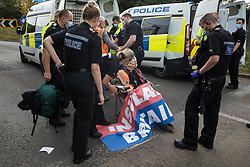 Godstone, UK. 13th September, 2021. Surrey Police officers prepare to arrest Insulate Britain climate activist Reverend Sue Parfitt who had blocked a slip road from the M25 as part of a new campaign intended to push the UK government to make significant legislative change to start lowering emissions. The activists, who wrote to Prime Minister Boris Johnson on 13th August, are demanding that the government immediately promises both to fully fund and ensure the insulation of all social housing in Britain by 2025 and to produce within four months a legally binding national plan to fully fund and ensure the full low-energy and low-carbon whole-house retrofit, with no externalised costs, of all homes in Britain by 2030 as part of a just transition to full decarbonisation of all parts of society and the economy.