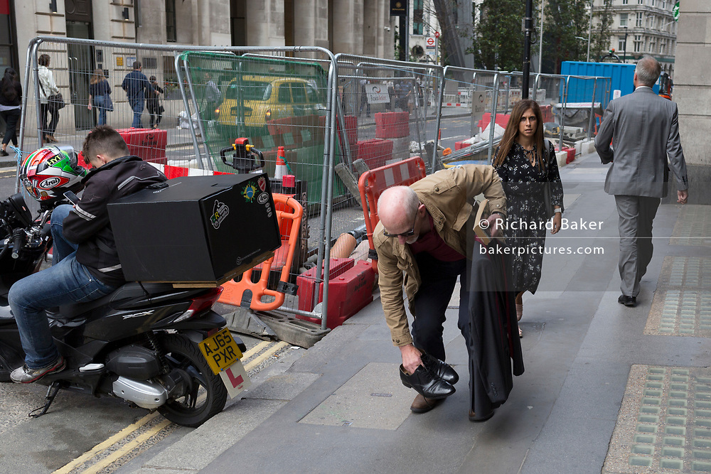 A man stoops to pick up his shoes from the pavement (sidewalk) on Leadenahall in the City of London, the capital's financial district - aka the Square Mile, on 8th August, in London, England.