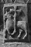 The Stone Bestiary - Black and white photo art print of Norman Romanesque exterior corbel no 39  -  sculpture of.an Angus Dei, the symbol of Jesus Christ as the Lamb of God. Strangely the creature holding the cross is a horse not a sheep. The sculpture is place in the centre of the Eastern Apse, symbolically the most important part of the church. The Norman Romanesque Church of St Mary and St David, Kilpeck Herefordshire, England. Built around 1140 .<br /> <br /> Visit our LANDSCAPE PHOTO ART PRINT COLLECTIONS for more wall art photos to browse https://funkystock.photoshelter.com/gallery-collection/Places-Landscape-Photo-art-Prints-by-Photographer-Paul-Williams/C00001WetsxVxNTo