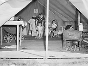 """9969-5150. """"Interior of a migratory laborer's tent, with Mrs. Raymond L Baker and her children. They left Indiana on May 5, 1940, coming to California and then to Oregon. May 29, 1941."""" United States Farm Security Administration mobile farm labor camp at North Plains, Oregon. May 29, 1941."""