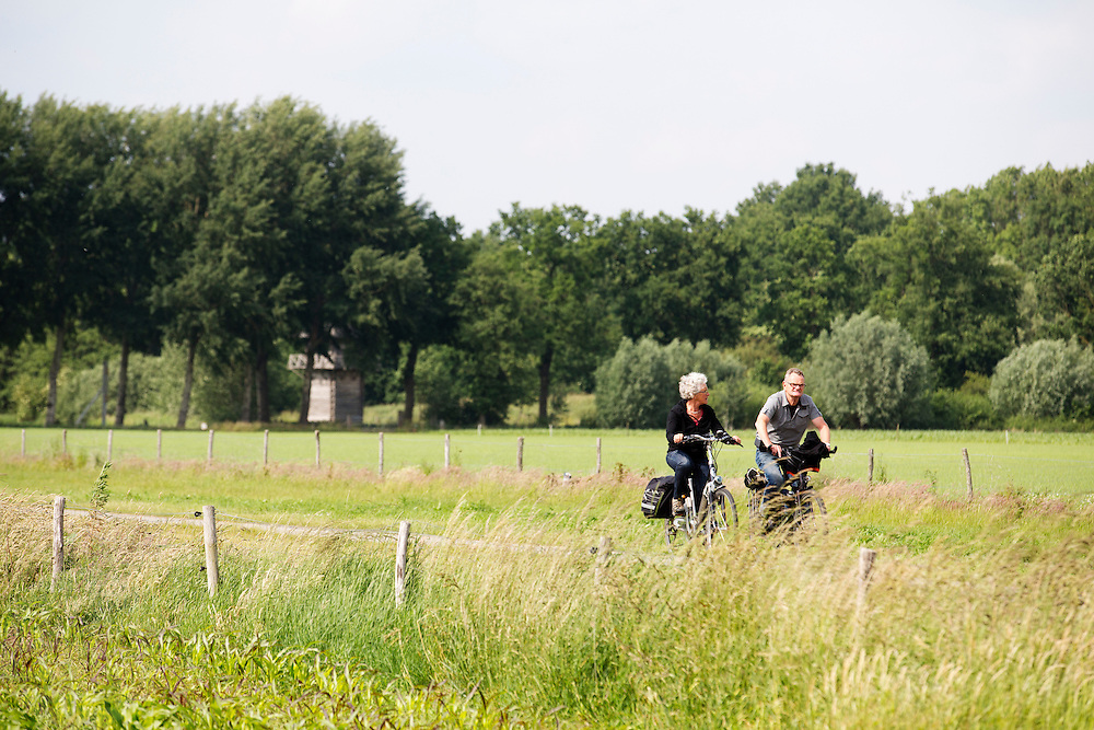 Bij Bunnik rijden fietsers door de weilanden.<br /> <br /> Near Bunnik cyclists ride at the pastures.