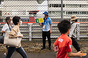 A staff member holds a sign about Covid-19 coronavirus countermeasures as fans walk towards the circuit during the men's cycling road individual time trial during the Tokyo 2020 Olympic Games at the Fuji International Speedway in Oyama, Shizuoka prefecture on July 28, 2021. - At the Fuji Speedway venue, around 100 kilometres (60 miles) from Tokyo, the rules on July 28 allowed for 10,000 spectators, less than half the venue's full capacity of 22,000. (Photo by Yuki IWAMURA / AFP)