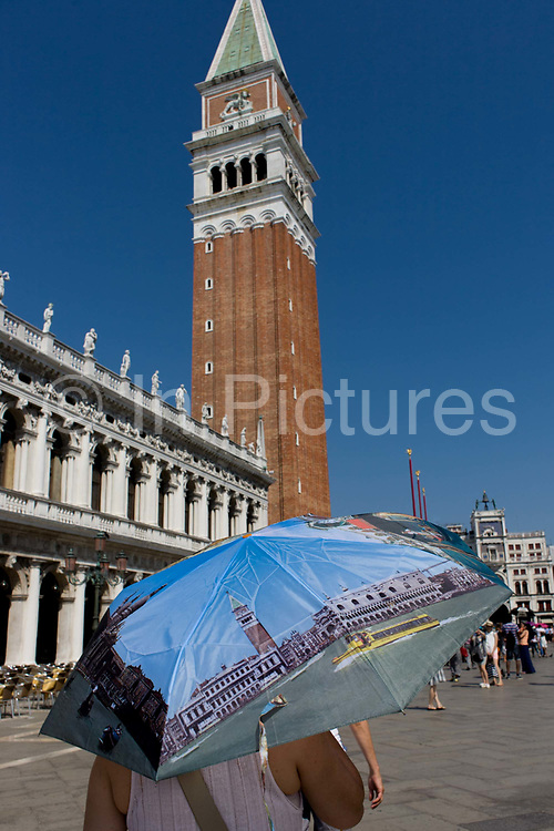 Tourist umbrella beneath the Campanile in Piazza San Marco, Venice, Italy. The wide expanse of Piazza San Marco is in the heart of Venice and where, for most daylight hours, the pavement is crowded with humanity as the influx of tourists who, in their own way, flood the narrow streets with sun-shading umbrellas and the smaller canals with gondolas. Venice attracts 22-million visitors each year (for a city of only about 60,000 residents) while the cultural protection organisation, Italian Nostra, warns that Venice can only accommodate about 33,000 visitors per day but currently at least 60,000 daily.