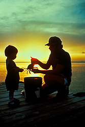 Stock photo of the silhouette of a young boy on a pier with his father holding a crab