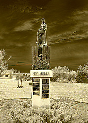 The statue of a a German Lutheran woman carrying a basket of field goods (grain, fruits, vegetables), and leading a child. She stands proper upon the Lutheran Bible, which is fronted by a three masted sailing ship which brought them from Germany. On the right side of the Book is an outline of the United States of American and on the left cover of the book is the outline of the Germanic States from which they sailed. Around the concrete pedestal top are the words NEW DREAMS NEW HOPES NEW MELE. The concrete column is adorned with brass plaques which proudly declare the persons and businesses than donated time and/or money for the completion of this statue.