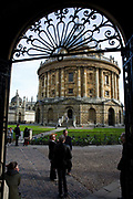 "Through Bodleian Library arch, we see visitors as they tour the famous Oxford landmark, the Radcliffe Camera as undergraduate students talk in the background and modern bicycle are chained to railings of this circular 16th century construction. The round building is in afternoon sunshine is foreground and the walls and towers of All Souls College is seen behind with its gold gates to the far left. The Radcliffe Camera (colloquially, ""Rad Cam""; ""Radder"" in 1930s slang) is a building in Oxford, England, designed by James Gibbs in the English Palladian style and built in 1737–1749 to house Oxford University's Radcliffe Science Library (source Wiki). Radcliffe Camera rises 150 feet (46 meters) above cobbled Radcliffe Square."
