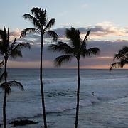 A surfer at sunset on Kauai.