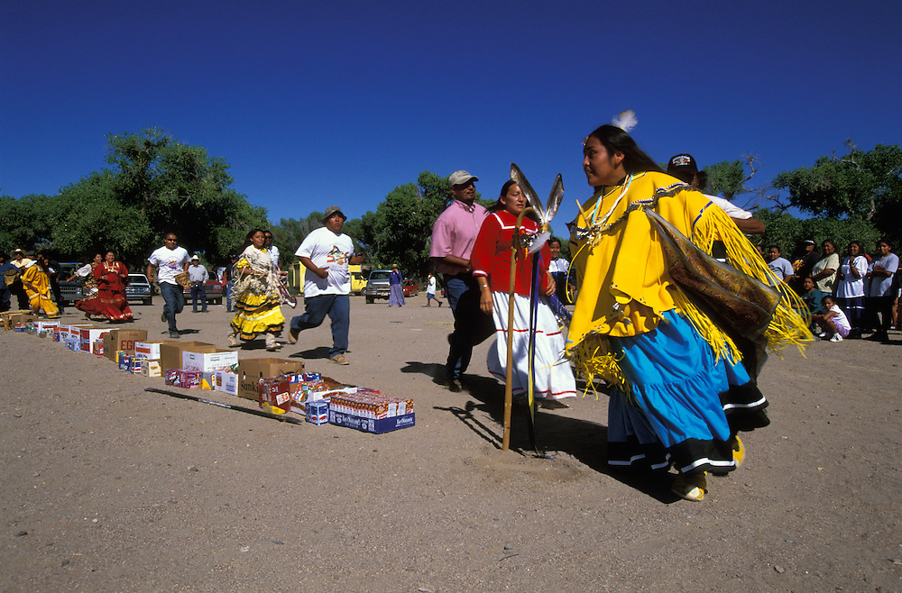 An Apache girl, dressed in buckskin dress, runs during her Sunrise Dance, a first menstruation rite, on the San Carlos Apache Indian Reservation in Arizona, USA. She runs four times, each time a little bit longer. This symbolises the four stages of life. Close behind her godmother and relatives  follow, the women dressed in camp dresses. The food, snacks and drinks on the ground symbolise a life without material want. The Sunrise Dance is supposed to prepare the girl for adulthood and to give her a long and healthy life. The ceremony is also an enactment of the Apache creation myth and during the rites the girl 'becomes' Changing Woman, a mythical female figure, and comes into possession of her healing powers.