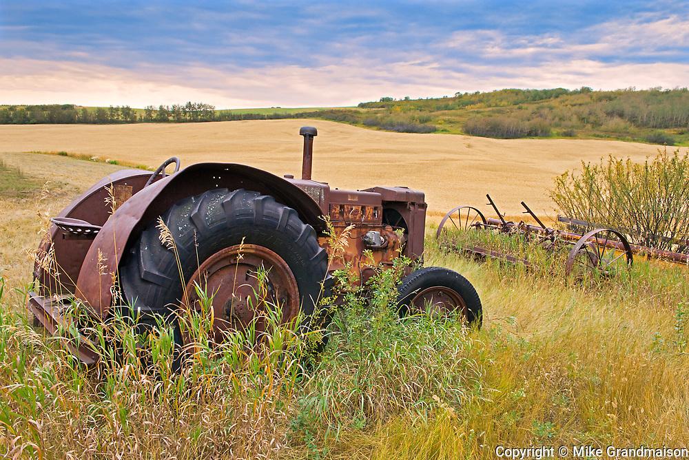 Tractor and old farm implements on homestead<br />Baljennie<br />Saskatchewan<br />Canada