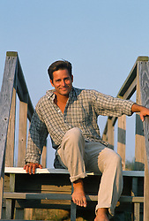 Smiling young man sitting on wooden steps