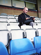A supporter reading a football programme ahead of Dulwich Hamlet FC vs Hendon at Champion Hill on 12th September 2017 in South London in the United Kingdom. Dulwich Hamlet was founded in 1893 and both teams play in the Isthmian League Premier Division, a regional mens football league covering London, East and South East England.