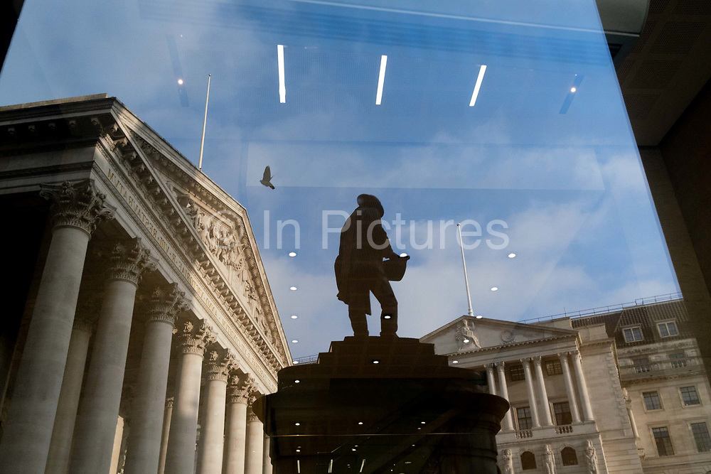 Days before the Chancellor Rishi Sunak delivers his Budget, Royal Exchage left and the Bank of England right are seen reflected in an office propertys window along with the silhouetted statue of  civil engineer James Henry Greathead, on 1st March 2021, in London, England. James Henry Greathead 1844 – 1896, renowned for his work on the London Underground.