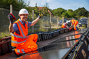Leo Murray, director of innovation at 10:10 Climate Action cleaning the array of solar panels next to the line near Aldershot Railway Station.  This innovative project is the first in the UK to power the railway with electricity generated from solar power and, if successful, could see many Network Rail sites across the country adapting this sustainable energy approach. Riding Sunbeams is a social enterprise, run by 10:10 Climate Action. Built with Community Energy South and partnered with Network Rail and The Department for Transport and by InnovateUK.  Aldershot, Hampshire, United Kingdom. Riding Sunbeams is a world leading project to connect solar panels directly into electrified rail routes to power the trains. Direct supply of solar power to rail traction systems has never been done. But it has huge potential - from metros, trams and railways in the UK and around the world.<br /> (photo by Andrew Aitchison / In Pictures via Getty Images)