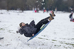 © Licensed to London News Pictures. 24/01/2021. Epsom, UK. A snow boogie boarder gets airborne in the snowy conditions on Epsom Downs in Surrey. A band of snow is crossing the south east this morning as temperature remain just above freezing. Photo credit: Peter Macdiarmid/LNP