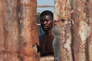 Ahmed Alheji, a migrant from Nigeria who has lived in the Rosarno ghetto since 2012, looks through a ruined metal sheet of a burnt shack on August 9, 2017 in Reggio Calabria, Italy. The San Ferdinando Camp, better known as the Rosarno ghetto, is located in the Plain of Gioia Tauro and hosts 600 migrants in summer, and as many as 2000 in winter. Living conditions in the camp are now appalling due to the recent hot weather in southern Italy, and have further deteriorated after a fire in July destroyed two-thirds of the camp, making it virtually uninhabitable on health and humanitarian grounds. Italian Civil Protection is building the new camp that will host up to 600 people. ©Simone Padovani