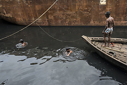 June 3, 2017 - Dhaka, Dhaka, Bangladesh - Shipyard workers working in the polluted river Buriganga in Dhaka, Bangladesh. The River Buriganga, which runs past Dhaka City, is at present one of the most polluted rivers in Bangladesh. The City of Dhaka discharge about 4,500 tons of solid waste every day and most of it is released into the Buriganga. The water of this river is now so polluted that all fish have died, and increasing filth and human waste have turned it like a black gel. Even rowing across the river is now difficult for it smells so badly. (Credit Image: © Probal Rashid via ZUMA Wire)