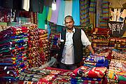 Stallholder drinking chai in shop selling prayer mats at muslim Meena Bazar, in Old Delhi, India