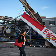 Woman walks past an Exxon gas station that collapsed in Whitestone, Queens in New York on Thursday, September 2, 2021. John Taggart for The New York Times<br /> <br /> NYCFLOODS