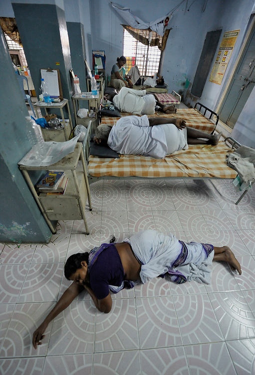 T Hynavathi, a staff member of the Lutheran Counseling and Health Care Center in Chilakaluripet, a town in Andhra Pradesh, India, rests on the floor after attending to AIDS patients in the center's clinic.