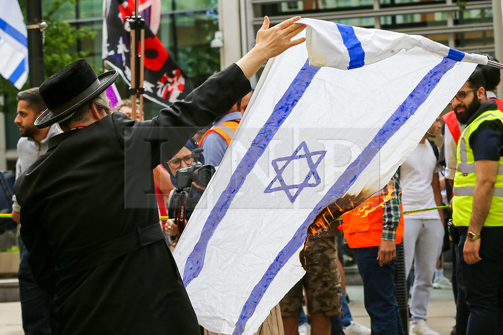 © Licensed to London News Pictures. 02/06/2019. London, UK. Protesters burn the Israel flag. <br /> Protesters take part in the annual Al Quds day protest and march from Home Office to Whitehall in central London. Al-Quds Day, an annual day of protest decreed in 1979 by the late Iranian ruler Ayatollah Khomeini, is celebrated to express support for the Palestinian people and their resistance against Israeli occupation. A counter demonstration by Israel supporters takes place. Photo credit: Dinendra Haria/LNP