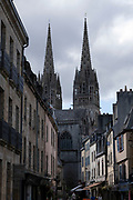 Street scene outside with Saint Corentin Cathedral on 24th September 2021 in Quimper, Brittany, France. Gothic cathedral, begun in 1239, with soaring twin spires. Quimper is the ancient capital of Cornouaille, Brittany's most traditional region, and has a distinctive Breton Celtic character. Its name is the Breton word Kemper, meaning confluence. Brittany is a peninsula, historical county, and cultural area in the west of France, covering the western part of what was known as Armorica during the period of Roman occupation. It became an independent kingdom and then a duchy before being united with the Kingdom of France in 1532 as a province governed as a separate nation under the crown.