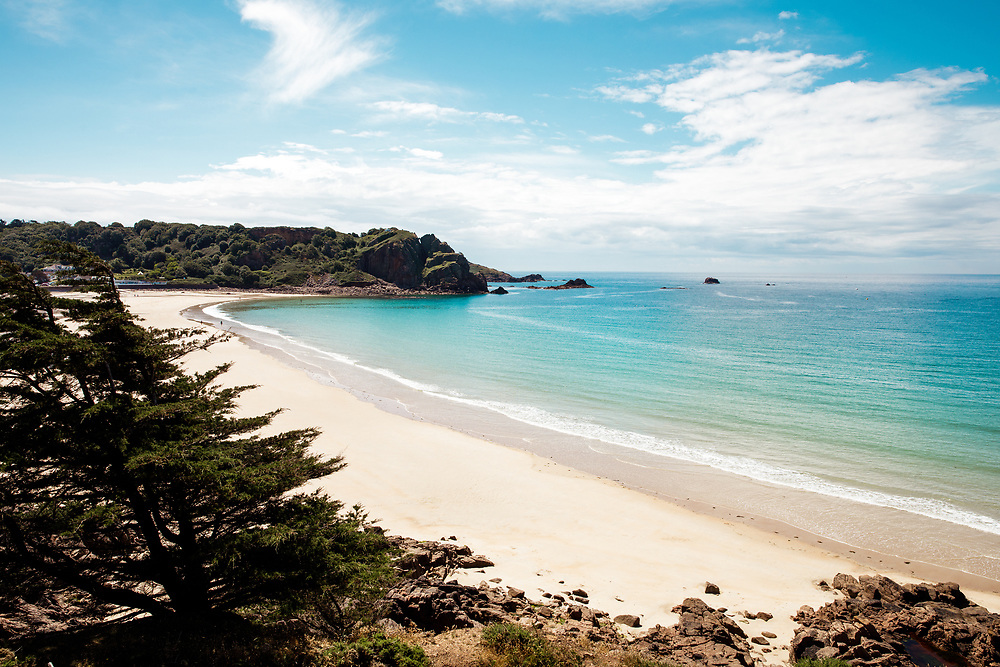 View across Ouaisne Bay, a paradise beach with white sand and turquoise calm, clear water on a sunny day in Jersey, Channel Islands