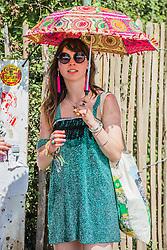 The sun comes back out and umbrellas/parasols return. The 2015 Glastonbury Festival, Worthy Farm, Glastonbury.