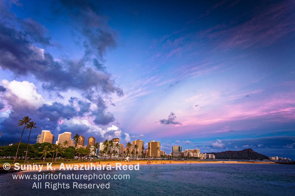 Pastel sky over Magic Island Beach and Waikiki skyline. Diamond Head is in the background. Honolulu, Oahu Island, Hawaii.