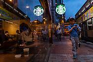 Hong Kong - August 16, 2019: Pedestrians walk at dusk past a Starbucks on Gloucester Road in the Wan Chai area of Hong Kong Island.