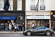Japanes tourists photograph a silver Ferrari outside shops on New Bond Street, central London