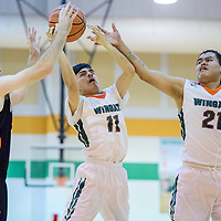 Wingate Bears Matthew Begay (11) and Leon Alonzo (21) grab a rebound away from Aztec Tiger Chad Hill (22) Tuesday at Wingate High School.