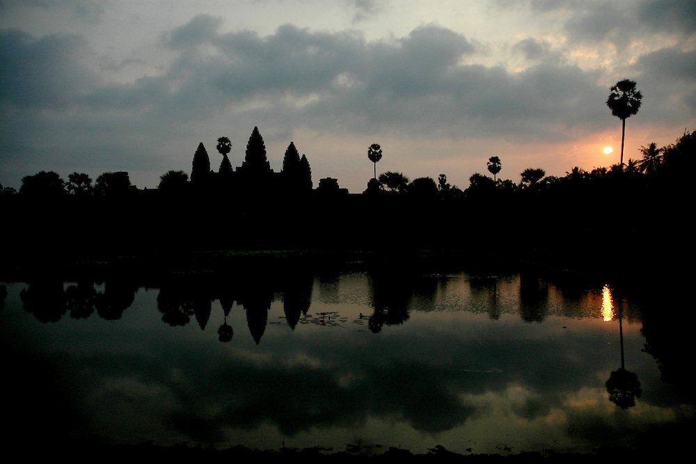 This sunrise shot of Angkor Wat, the world's largest single religious monument located in Siem Reap, Cambodia was shot in front of the Northern reflecting pond located off the path to the central towers.<br /> <br /> Angkor Wat was built for the king Suryavarman II in the early 12th century as his state temple and capital city.<br /> <br /> It is a massive three-tiered pyramid crowned by five lotus-like towers rising 65 meters from ground level is surrounded by a moat and an exterior wall. All the walls of the temple are covered inside and out with bas-reliefs and carvings. <br /> <br /> Angkor Wat has become a symbol of Cambodia, appearing on its national flag and is worthy of all it's attention. <br /> <br /> It is one of the most awe-inspiring locations I have ever been. From the sunrise to the sunset, there isn't a time of day that is not simply a spectacular time to explore this breathtaking location.