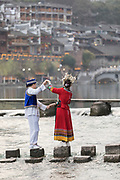 Rear view of a boy and a girl in traditional Miao clothing posing on stepping stones in a river, Fenghuang, Hunan Province, China