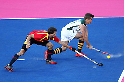 Lloyd Norris-Jones of South Africa tries to get the cross through during Pool MA Hockey  match between South Africa and Spain held at the Riverbank Arena in Olympic Park in London as part of the London 2012 Olympics on the 3rd August 2012..Photo by Ron Gaunt/SPORTZPICS