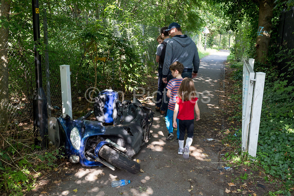 A family walk past a crashed motorbike scooter left abandoned on a path in south London, on 2nd September 2017, in London, England.
