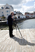 Photographer with camera and tripod Swanage, Dorset, England