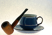 still life, Old wooden pipe and a cup of coffee on white background