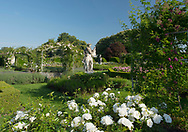 Rosa 'Iceberg', rose covered arches and statues in the rose parterre in the walled garden at Houghton Hall, King's Lynn, Norfolk, UK