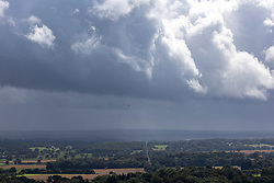 Licensed to London News Pictures. 30/07/2021. Dorking, UK. Gloomy views from Box Hill over Surrey today as an unseasonable storm hit the South Coast today. Storm Evert hit the South Coast of England this morning with winds speed in excess of 65mph as the Met Office issue weather warnings for high winds, coastal gales and heavy rain with disruption to travel. Photo credit: Alex Lentati/LNP