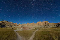 Moonlight illuminates the badlands and grassland in South Dakota.