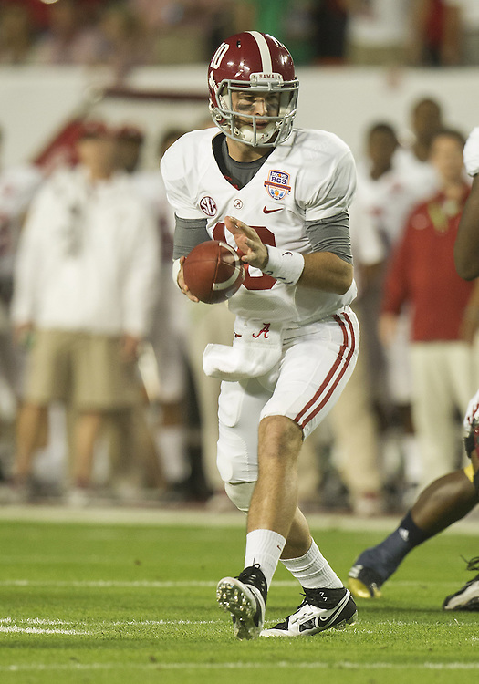 January 7, 2013:  Alabama quarterback AJ McCarron (10) pivots to hand the ball off during the Discover BCS National Championship between the Alabama Crimson Tide and the Notre Dame Fighting Irish at Sun Life Stadium in Miami Gardens, Florida.  Alabama defeated Notre Dame 42-14.