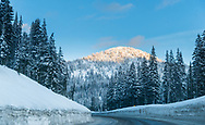 Sunset light on a winter evening over the icy road at Kootenay Pass on the Crowsnest Highway in Southern British Columbia, Canada