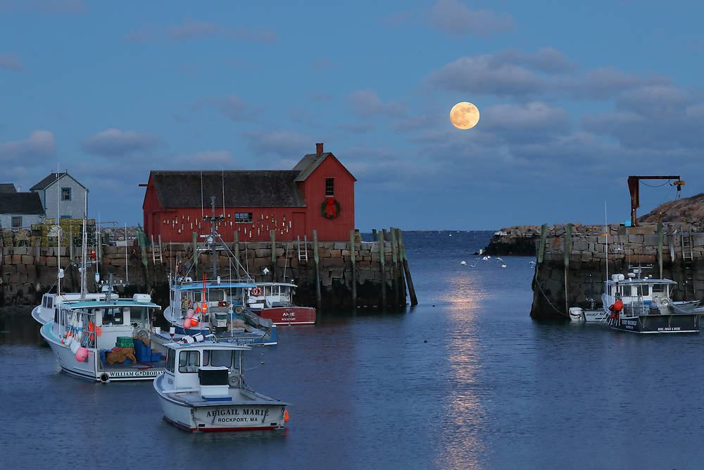 This New England photography image of Rockport Motif #2 with a rising full moon is available as museum quality photography prints, canvas prints, acrylic prints, wood prints or metal prints. Prints may be framed and matted to the individual liking and decorating needs: <br /> <br /> https://juergen-roth.pixels.com/featured/1-rockport-massachusetts-juergen-roth.html<br /> <br /> New England harbor scenery photography of this famous red fishing shack in Rockport, MA on Cape Ann was photographed on a bitter cold night in January. The historic landmark is known throughout New England as Motif #1, so called because it is the most often painted building in America.<br /> <br /> Good light and happy photo making!<br /> <br /> My best,<br /> <br /> Juergen<br /> Licensing: http://www.rothgalleries.com<br /> Photo Prints: http://fineartamerica.com/profiles/juergen-roth.html<br /> Photo Blog: http://whereintheworldisjuergen.blogspot.com<br /> Instagram: https://www.instagram.com/rothgalleries<br /> Twitter: https://twitter.com/naturefineart<br /> Facebook: https://www.facebook.com/naturefineart