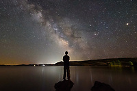 The milky way glowed above Lake DeSmet, Wyoming, on a summer night. The red planet Mars is visible on the far right. I stood on a small rock in the lake for this self portrait.