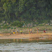 A group of boys play a ballgame on a sandbank island in the middles of the Mekong River near Luang Prabang in central Laos.