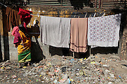 A woman hangs some clothes out to dry.  The slum of Cheetah Camp on the outskirts of Mumbai, India is a predominantly muslim community on living on the fringe while the city continues to grow.