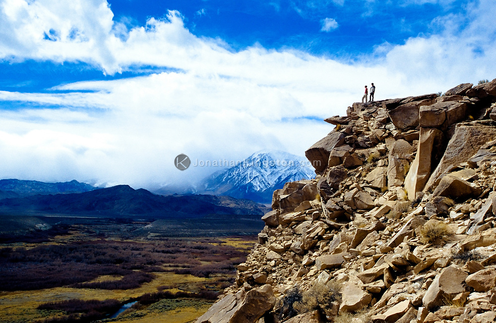 A couple stands on top of a lava butte known as the Volcanic Tablelands, overlooking the Owens river valley with a view of snow capped Mt. Tom in the background, Bishop, California. (releasecode: jk_mr1016, jk_mr1029) (Model Released)