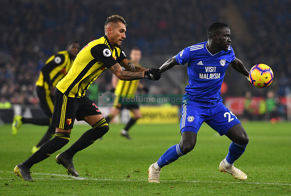 Watford's Roberto Pereyra (left) pulls Cardiff City's Oumar Niasse during the Premier League match at the Cardiff City Stadium.