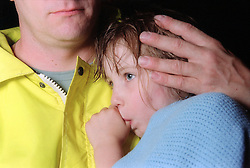 Young girl wrapped in blanket sucking thumb being comforted by worker from emergency services,